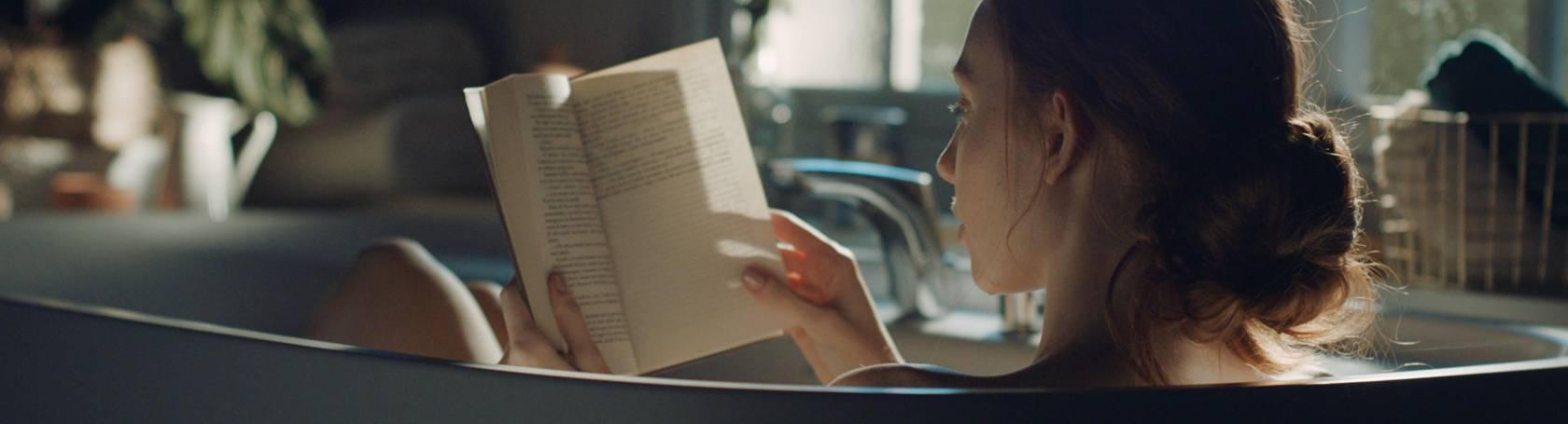 Mujer leyendo libro en bañera Roca